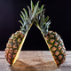 Tropical ripe fruit pineapple with green leaves presented on a wooden table around a dark background - PhotoDune Item for Sale