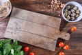 Wooden board on the kitchen table around boiled quail eggs in a bowl, pieces of nuts, tomatoes, meat - PhotoDune Item for Sale
