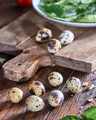 Quail eggs and greens in a plate on a wooden table. Ingredients for Making Healthy Salad - PhotoDune Item for Sale