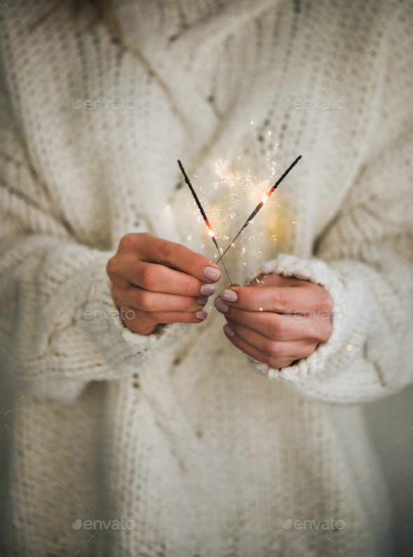 Woman in sweater holding Christmas sparklers in hands, close-up - Stock Photo - Images