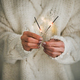 Woman in sweater holding Christmas sparklers in hands, close-up - PhotoDune Item for Sale