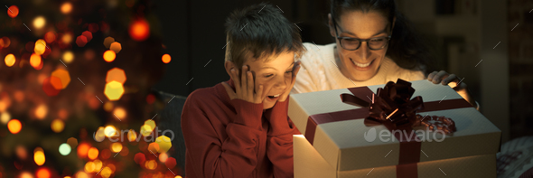 Boy and his mom opening a beautiful Christmas gift - Stock Photo - Images