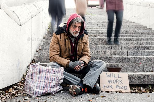 Homeless beggar man sitting outdoors in city asking for