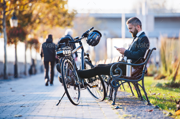 Businessman commuter with bicycle sitting on bench in city, using smartphone. - Stock Photo - Images