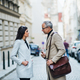 Man and woman business partners standing outdoors in city of Prague, talking. - PhotoDune Item for Sale