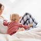 A young mother with little daughter sitting indoors on bed in the morning, playing. - PhotoDune Item for Sale