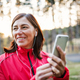 A female runner with earphones outdoors in autumn nature, using smartphone. - PhotoDune Item for Sale