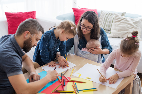 A portrait of young family with small children around table indoors, drawing. - Stock Photo - Images
