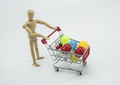 Wooden dummy carries shopping cart with pills, insulated on white background, conceptual image - PhotoDune Item for Sale