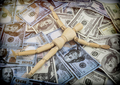 Doll made of wood lying on a lot of banknotes of dollar Americans, conceptual image - PhotoDune Item for Sale