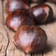 bunch of chestnuts ready to be roasted on rustic wood - PhotoDune Item for Sale