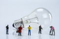 Miniature figures near a light bulb, conceptual image - PhotoDune Item for Sale