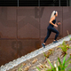 Fit sports women running interval workout in stairs against a metal wall in city - PhotoDune Item for Sale