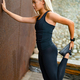 Fitness woman stretching after workout against metal wall in the city - PhotoDune Item for Sale