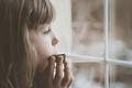Sad girl playing harmonica by the window - PhotoDune Item for Sale