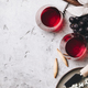 Free Download Glasses of red wine, cheese and grapes on rustic concrete backgr Nulled
