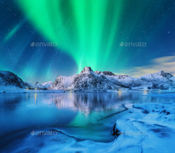 Aurora borealis over snowy mountains, frozen sea coast - Stock Photo - Images