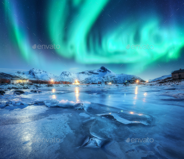 Northern lights above snowy mountains, frozen sea coast - Stock Photo - Images
