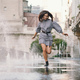 Free Download girl playing and dancing around on a wet street Nulled