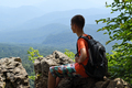 Boy sitting on edge of cliff with backpack and looks at mountains - PhotoDune Item for Sale