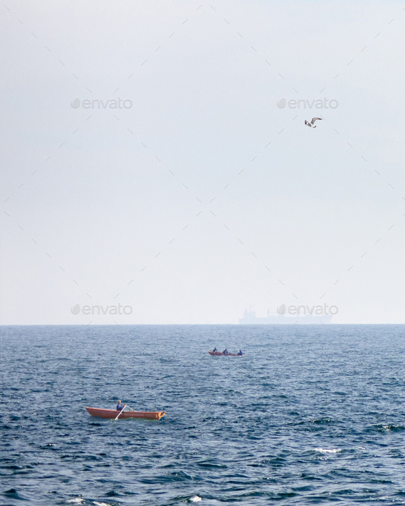 View of fishing boats on a background of blue open sea and a tanker blurred on the horizon - Stock Photo - Images