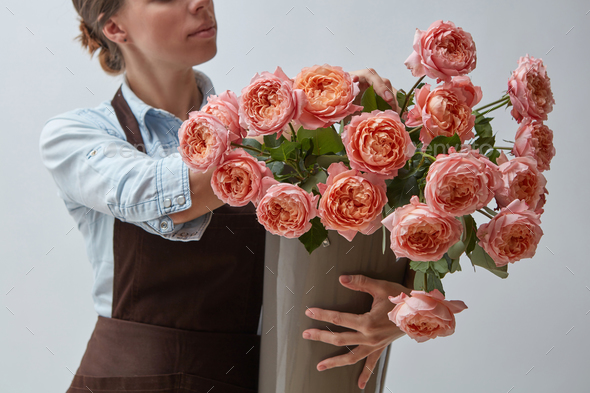 Girl florist with a big bouquet of pink roses around a gray background. The concept of a flower shop - Stock Photo - Images