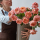 Girl florist with a big bouquet of pink roses around a gray background. The concept of a flower shop - PhotoDune Item for Sale