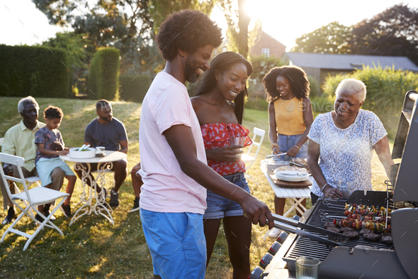 Couple grilling at a black multi generation family barbecue - Stock Photo - Images