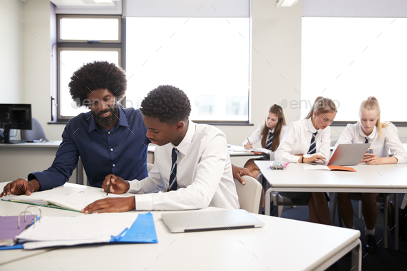 High School Tutor Giving Uniformed Male Student One To One Tuition At Desk In Classroom - Stock Photo - Images