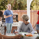 Family at a table outdoors turn to dad standing by barbecue - PhotoDune Item for Sale