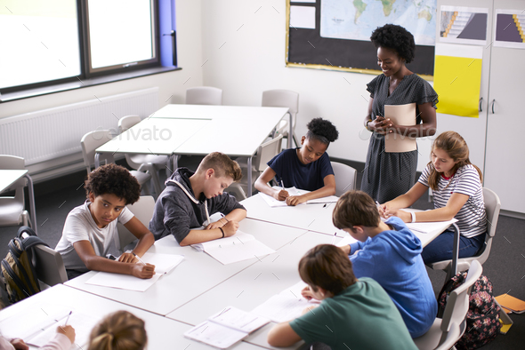 Female High School Tutor Standing By Table With Students Teaching Lesson - Stock Photo - Images