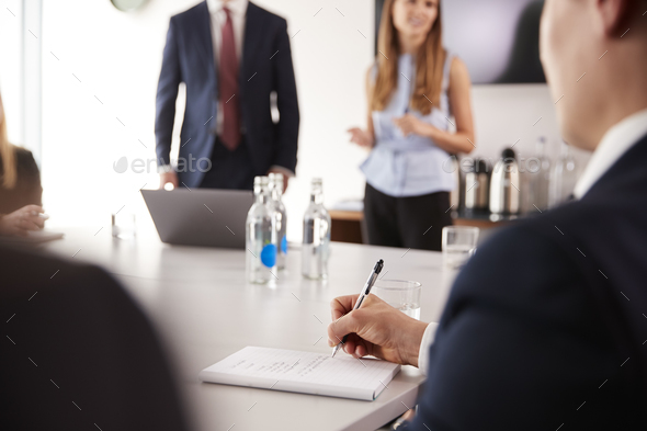 Businessman Making Notes At Group Meeting Around Table On Graduate Recruitment Assessment Day - Stock Photo - Images