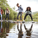 Multi ethnic group of five young adult friends laughing as they balance on rocks to cross a stream - PhotoDune Item for Sale