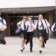 Group Of High School Students Wearing Uniform Running Out Of School Buildings  - PhotoDune Item for Sale