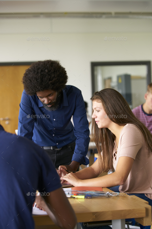 Teacher Talking To Female High School Student Sitting At Work Bench Using Laptop  - Stock Photo - Images