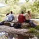 Five young adult friends taking a break sitting on rocks by a stream during a hike - PhotoDune Item for Sale