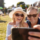 Mature Couple Sitting On Rug At Summer Garden Fete Taking Selfie On Mobile Phone - PhotoDune Item for Sale