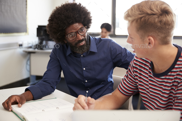 High School Tutor Giving Male Student One To One Tuition At Desk  In Classroom - Stock Photo - Images