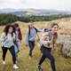 Multi ethnic group of five young adult friends hiking across a field  - PhotoDune Item for Sale