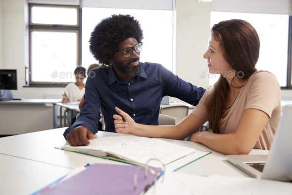High School Tutor Giving Female Student One To One Tuition At Desk  In Classroom - Stock Photo - Images