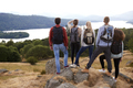 A group of five mixed race young adult friends admire the view after arriving at summit  - PhotoDune Item for Sale