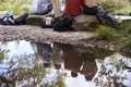 Reflection in stream of five young adult friends taking a break sitting on rocks during a hike - PhotoDune Item for Sale