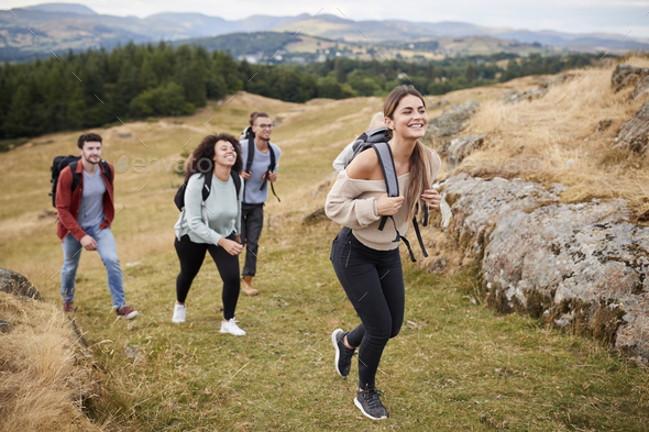 Multi ethnic group of five young adult friends hiking across a field uphill towards the summit - Stock Photo - Images