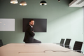 Portrait Of Young Businessman Sitting On Boardroom Table At Graduate Recruitment Day - PhotoDune Item for Sale