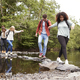 Five mixed race young adult friends hold hands and help each other while crossing a stream  - PhotoDune Item for Sale