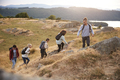 A multi ethnic group  of five young adult friends smile while climbing to the summit - PhotoDune Item for Sale