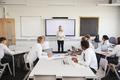 Female High School Teacher Standing Next To Interactive Whiteboard  - PhotoDune Item for Sale