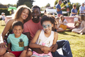Portrait Of Family With Children Sitting On Rug At Summer Garden Fete - PhotoDune Item for Sale