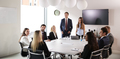 Group Of Young Businessmen And Businesswomen Meeting Around Table  - PhotoDune Item for Sale