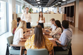 Businessman And Businesswoman Addressing Group Of Young Candidates Sitting Around Table  - PhotoDune Item for Sale